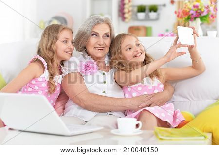 granny with her granddaughters making selfie with smartphone