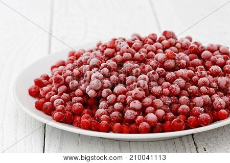 Closeup Of Frozen Redcurrants On White Ceramic Plate On White Painted Table.