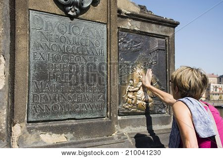 Woman Touching On The Plaque Under St. John Of Nepomuk Statue Is Supposed To Bring Good Luck And Ens