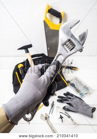 close-up Allen wrench in hand with glove on the background of the bag with the tool