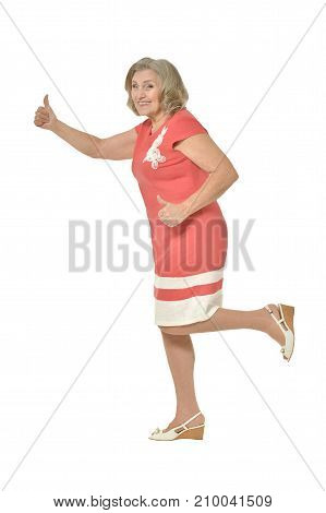 Beautiful senior woman in pink dress showing thumbs up isolated on white background