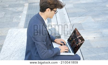 Handsome young man sitting on a stone bench working outdoors in an urban setting typing information onto his laptop computer