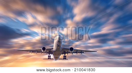 Airplane and beautiful sky with motion blur effect. Landscape with flying passenger airplane and blurred blue sky with colorful clouds at sunrise. Passenger airliner. Commercial aircraft. Private jet