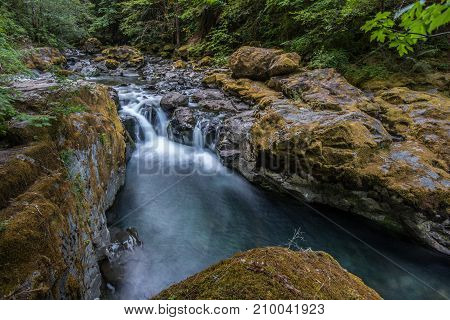 Water Cascading Over Mossy Rocks In Brice Creek