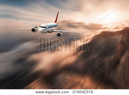 Modern airplane mith motion blur effect is flying over low clouds at sunset. Landscape with passenger airplane, blurred clouds, mountains, sun. Passenger aircraft. Commercial plane. Vintage style