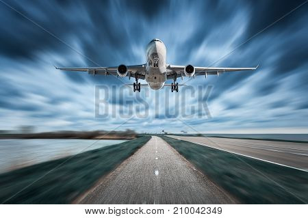 Airplane and road with motion blur effect in overcast. Landscape with passenger airplane is flying over the asphalt road and cloudy sky. Commercial plane is landing. Aircraft with blurred background