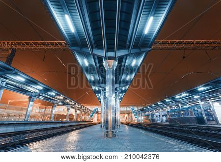 Modern futuristic railway station with illumination in fog at night in Europe. Amazing industrial landscape with railway platform, railroad, sky, city lights and building. Railway transportation