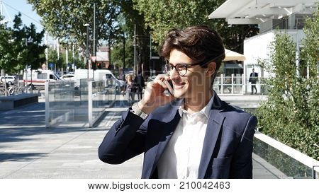 Handsome trendy businessman wearing white shirt and suit jacket, standing and talking on cell phone, outdoor in city setting