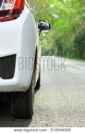 Front of white car parking on asphalt road