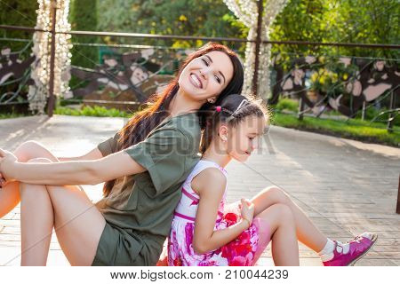 Attractive mother and daughter sitting back to back in arbour, they smiling, having fun and very happy