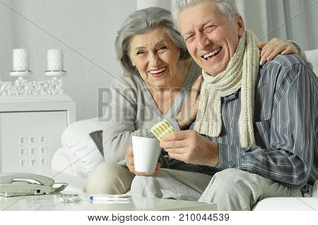Ill senior couple sitting at table and taking pills