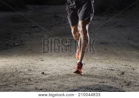 front view of sport man with ripped athletic and muscular legs running off road in jogging training workout at countryside on earth soil in harsh fitness and healthy lifestyle concept dramatic light