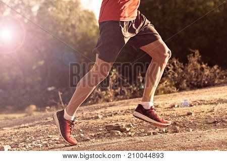 side view of sport man with ripped athletic and muscular legs running uphill off road in jogging training workout at countryside in Autumn background in fitness and healthy lifestyle concept