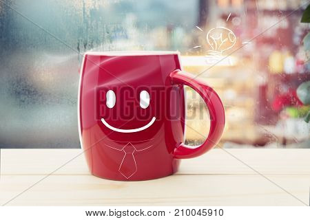 Red mug of coffee with a happy smile Steaming red coffee cup on a rainy day window background Good morning and Business concept