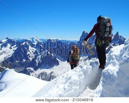 CHAMONIX MONT BLANC, FRANCE EUROPE on JULY 2016: Two alpinists and mountaineer climber on AIGUILLE DU MIDI french ALPS top alpine mountains range landscape with clear blue sky in warm sunny summer day.