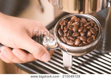 Roasted coffee bean in a portafilter prepare for making coffee from espresso machine