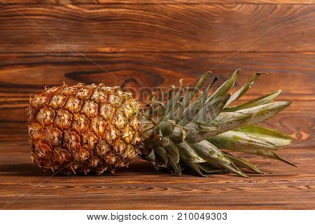 Close-up of pineapple on a wooden brown background in a horizontal position.