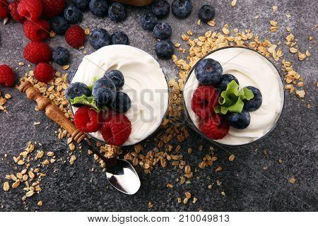 Glass jar of homemade granola with yogurt and fresh berries