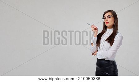 Businesswoman thinks on a gray background. Emotions.