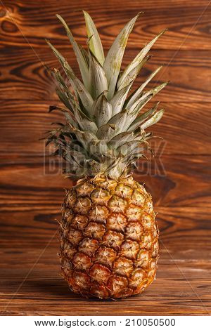 Close-up of a pineapple on a wooden brown background in an upright position.