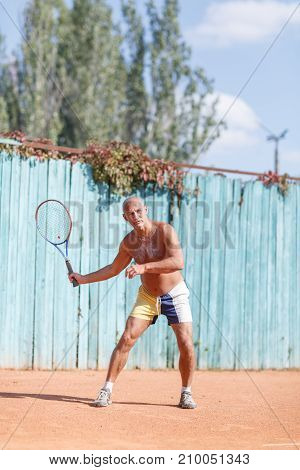 Senior men without a T-shirt beat the ball on the tennis court. In full growth. Sport concept.