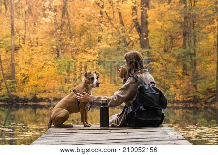 Tourist hiker girl sits at riverbank with her pet and enjoys beautiful indian summer sight with cup of coffee from thermos. Young female on a trip to nature park having rest near lake with her dog and looking at bright yellow autumn trees