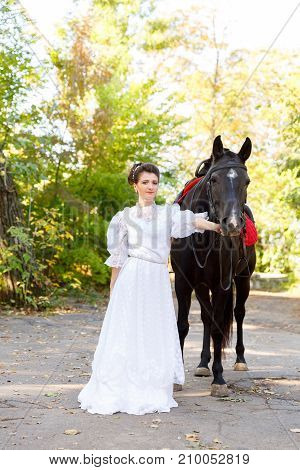 A beautiful bride in a dress with gathered hair leads a bridle horse. The concept of a wedding.