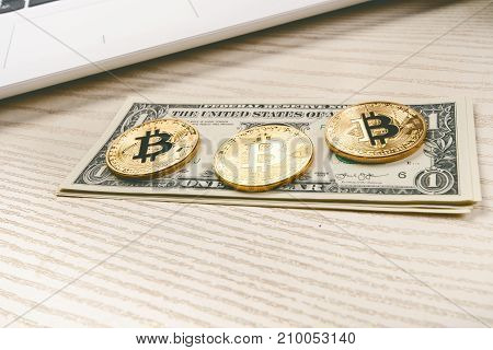 Bitcoin golden coins on a table with dollar banknotes and laptop. Virtual money. Cryptocurrency business. Office background.