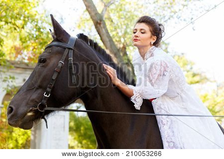 Beautiful bride in a wedding white dress riding a horse. The concept of a wedding. The girl is stroking the horse. Close-up.