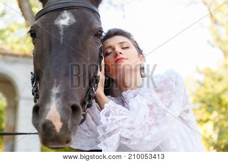 Portrait of a beautiful bride, brunette and horse. Close-up. The concept of a wedding. Bottom view.