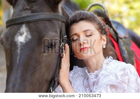 Portrait of a beautiful bride, brunette and horse. Close-up. The concept of a wedding.