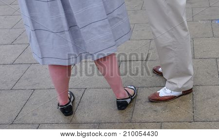 Couple wearing fancy shoes standing on paving stones Shot shows legs only.