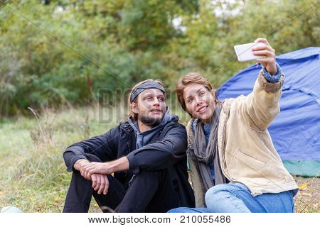 Couple in the forest near a camping tent. And photographing together. Girl with short hair.