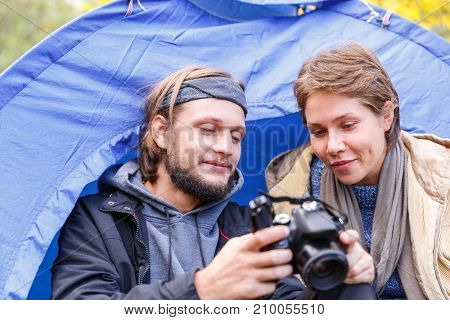 A young couple of tourists in the forest watching photos on a camera on the background of a tent. Close-up.