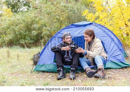 A young couple of tourists in the forest watching photos on a camera on the background of a tent.