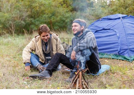 Couple relaxing in the forest. A loving couple is sitting in front of the tent. Conversation. The concept of adventure. Tourism. Field fire.