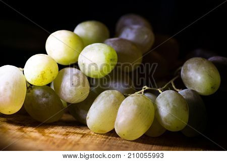 green grapes on a black background on a yellow wooden board macro shot