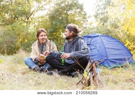 Couple relaxing in the forest. A loving couple is sitting in front of the tent. A man is drinking beer, a girl is holding chips. Smiling. Recreation.