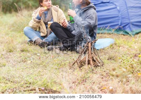 Couple relaxing in the forest. A loving couple is sitting in front of the tent. A man is drinking beer, a girl is eating chips. Smiling. Recreation.