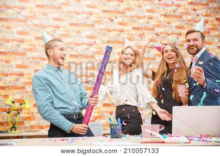 Young people celebrate something at a corporate party in the office. Close-up A young guy blows up a large confetti pittard.