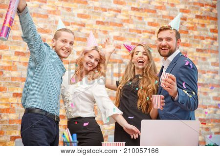 Young people celebrate something at a corporate party in the office. Merry. On their heads are wearing holiday caps.