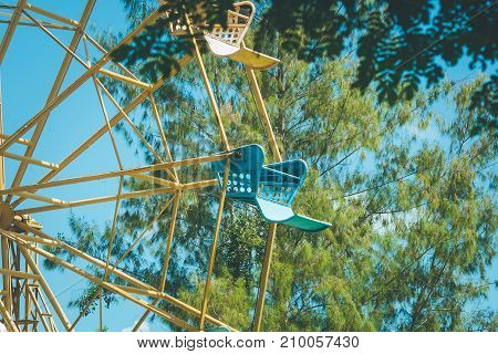 Vintage retro image close up part of colorful ferris wheel with green tree and blue sky background.