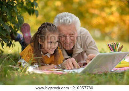 portrait of  girl  and  grandfather with a laptop in park
