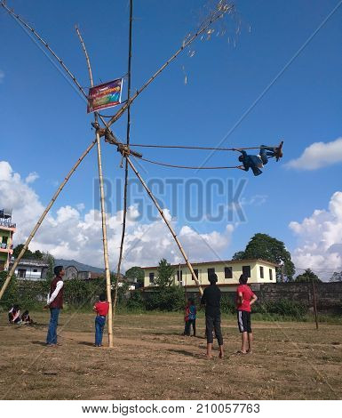Pokhara, Nepal - 21th October 2017 : Children playing on a traditional swing called Ping€ made of bamboo. Dashain festival celebration, an important event in the Nepalese calendar.