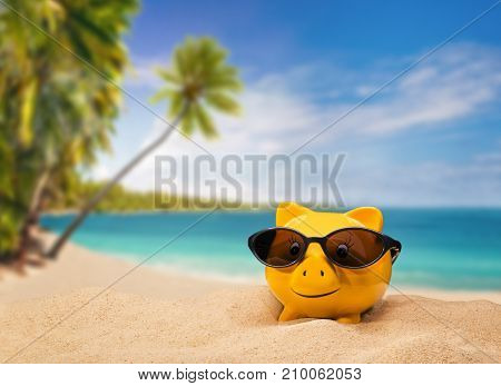 Yellow piggy bank with sunglasses with a tropical beach in the background