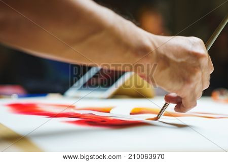 Artist makes the first brush strokes on a clean canvas while painting a watercolor painting. Concept of the school of painting.