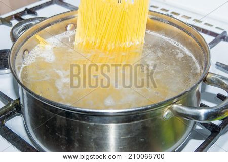 Spaghetti cooked in boiling water on a gas stove.