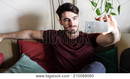 Attractive young man using cell phone to take selfie photo and send it, while laying on couch, smiling