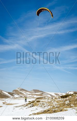 Skier rides with snow kite. Snowkiting. Vertical view.