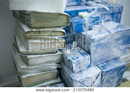 a stack of old books and blue gift boxes